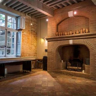 Décor tournage : salle avec grande cheminée en brique, salon Marvejol