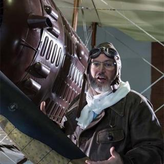 Décor pour votre tournage : un aviateur en costume d'époque à côté de son avion